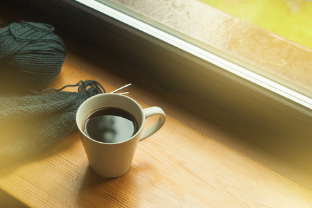Cup of coffee and knitting on windowsill, cozy morning, toned photo Stock Photo
