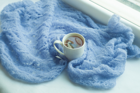 Cozy winter still life: mug of hot tea and warm woolen knitting on windowsill
