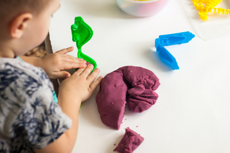 Happy kid with colorful clay toy, Art therapy for anxious children, cure for stress free