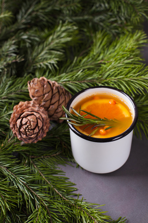White mulled wine with various spices on a grey background with fir tree ande cones. Hot alcoholic beverage, winter and fall, autumn drink