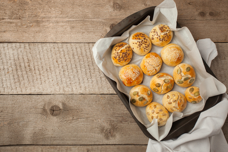 The homemade bread rolls with sesame seeds hamburger with sesame, pumpkin, flax, sunflower seeds on the tray, concept of burger and homemade food. Mini challah Stock Photo