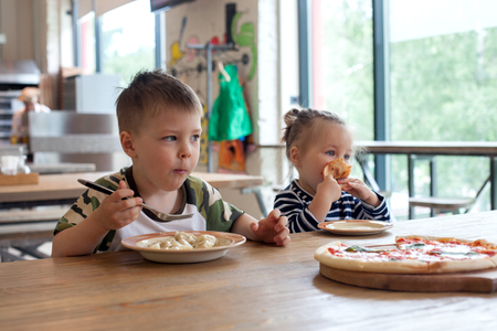 kids eat pizza and meat dumplings at cafe. children eating unhealthy food indoors. Siblings in the cafe, family holiday concept.