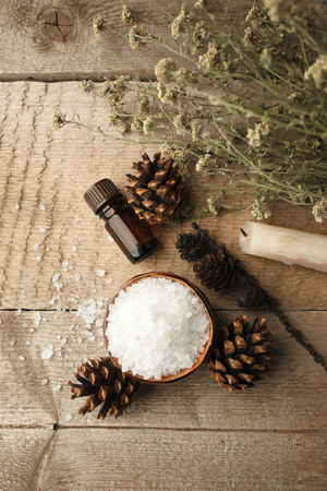 Spa and wellness setting with sea salt, oil essence, cones and candle on wooden background. Fall autumn wellness concept, Relax and treatment therapy. Close up Stock Photo
