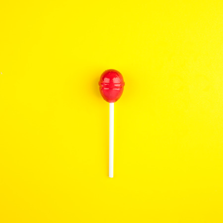 Colorful lollipop on bright yellow  background. Flat lay. Minimal summer concept.