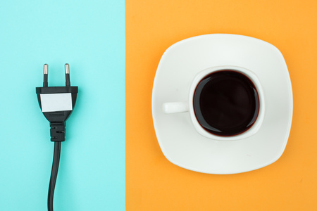 Trendy flat lay minimal concept, unplugged cord  and cup of coffee on bright background, concept of a break, rest from modern technologies