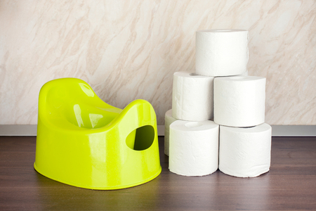 childrens toilet pot green and toilet paper, the concept of moving the baby from diapers to the toilet Stock Photo