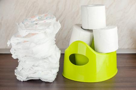 vaschetta igienica per bambini verde, pannolini e carta igienica, il concetto del passaggio del bambino dai pannolini al water
