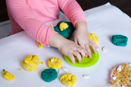 A 1.5 year old girl sits at a table and plays with a color test, on the table lie tools, molds and pasta for decor