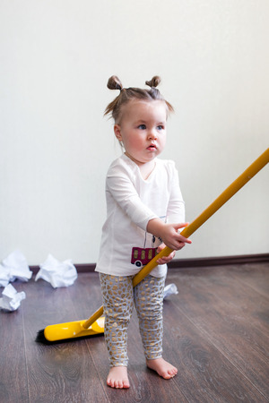 a girl holds a broom for 1.5 years, the concept of house cleaning, cleaning company, cleaning space, minimalism