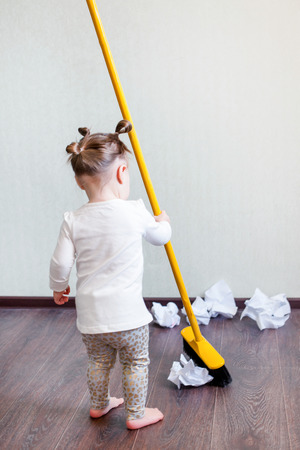 a girl holds a broom for 1.5 years, the concept of house cleaning, cleaning company, cleaning space, minimalism Stock Photo - 106756743