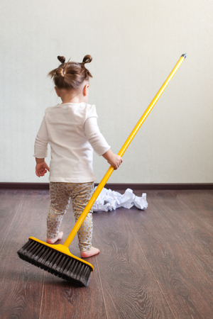 the child stands with his back to the camera, holds the broom in his hands and looks at the garbage Stock Photo