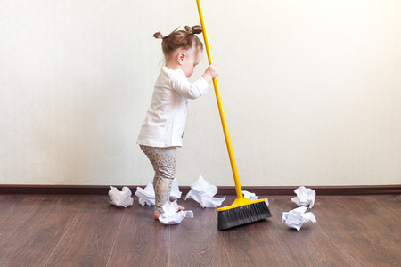 child sweeps broom with paper bins in the apartment, household chores
