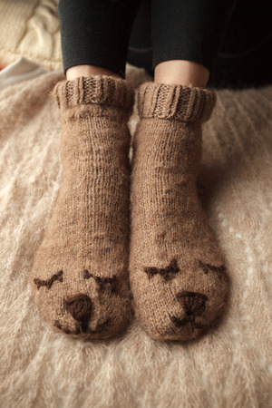 Cozy Winter fall autumn lifestyle: woman feets legs in warm cute bear socks. Retro toning, beige monochrome, hipster still life