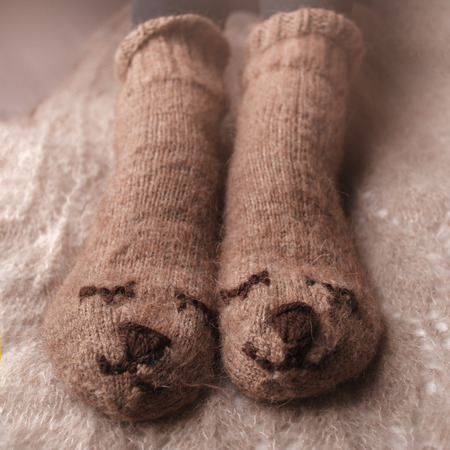 Cozy Winter fall autumn lifestyle: woman feets legs in warm cute bear socks. Retro toning, beige monochrome, hipster still life Stock Photo - 106963561