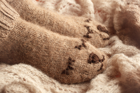 Cozy Winter fall autumn lifestyle: woman feets legs in warm cute bear socks. Retro toning, beige monochrome, hipster still life, season relax concept