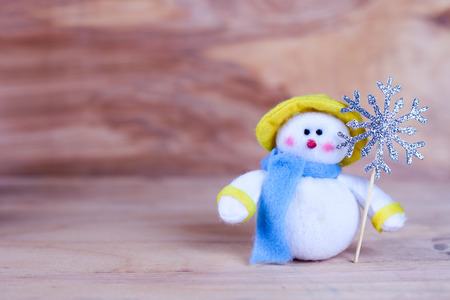 toy snowman with a blue scarf on a wooden background, opy space Stok Fotoğraf