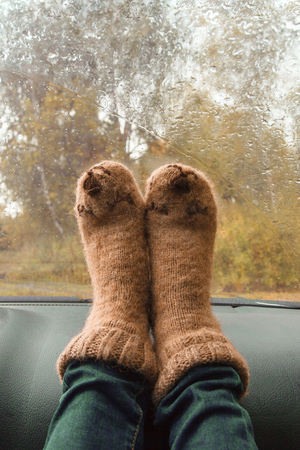Autumn car trip. Woman feet in warm wool socks in the car. Rain drops on windshield. Freedom travel concept. Autumn weekend. Stock Photo