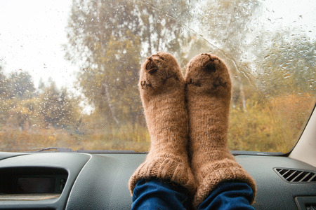Feet in warm cute socks on car dashboard. Travel, road trip and autumn fall concept. Stock Photo