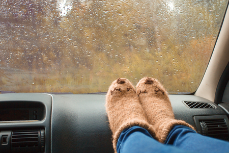 Woman legs in warm cute socks on car dashboard. Drinking warm tee on the way. Fall trip. Rain drops on windshield. Freedom travel concept. Autumn weekend