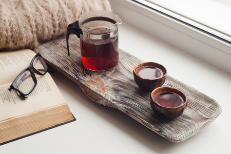 Still life details, cups of asian tea and teapot on vintage wooden tray on windowsill in living room. Lazy winter weekend with a book at home