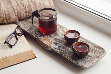 Stilleven details, kopjes Aziatische thee en theepot op vintage houten dienblad op vensterbank in de woonkamer. Lui winterweekend met een boek in huis Stockfoto