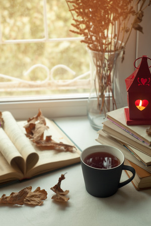 autumn still life. books, leaves, cuo of tea and dry tiny flowers in vase red candlestick with a burning candle on window. Concept of autumn reading time and romantic. Vertical, Warm, cozy window seat  opened book, light through shutters, rustic style home decor Stok Fotoğraf