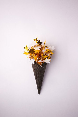 Black Ice Cream Cone with white gold star garland on white background, holiday party minimal closeup