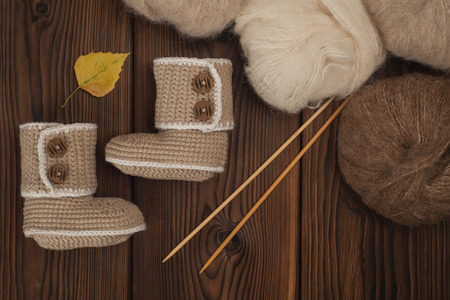 baby booties knitted by hand on a wooden background and skeins of wool