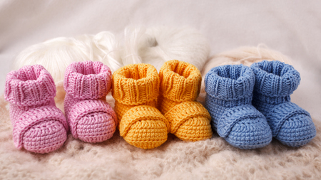 pregnancy concept, Three pairs of baby booties on a light background Banco de Imagens