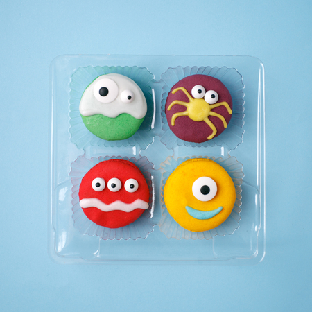 Heloween dessert: set of funny monsters, ghost, spider made of biscuits macaroon with icing and candy eyes close-up in plastic box on the table, party concept Stock Photo