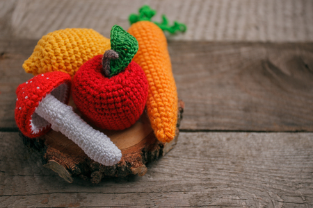 Set of knitted toys lemon, carrot, apple, amanita on wooden background. Earlier tactile development of children, craft toys, vegetarian menu concept, copy space