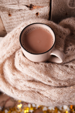 Details of still life in the home interior living room. Beautiful Cup of hot cocoa or chocolate and sweaters on wooden background . Cosy autumn-winter concept
