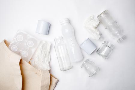 Raccolta differenziata: sacchetto di fazzoletti, confezione di uova, carta, bottiglia di vetro e lattina di alluminio. Concetto ecologico. Lay piatto Archivio Fotografico