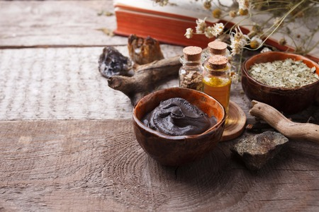 Preparing cosmetic black mud mask in ceramic bowl on vintage wooden  background. Front view of facial clay emulsion on table with spa products. Natural cosmetics for home or salon treatment Stockfoto