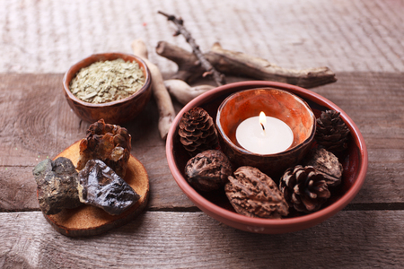 Healthy herbal tea preparation with dry plants, candle, wooden and stone details and vintage rustic wooden background, monochrome, relax concept