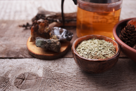 Herbal tea, homeopathy, alternative medicine, occult ritual concept/ Dry leaves in ceramic cup, stones, teapot on vintage wooden background, witchtable closeup Stock Photo