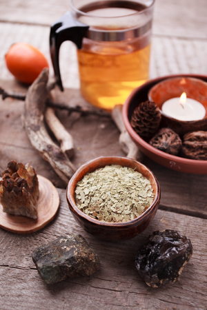 Healthy tea, dry herbs, plants and stones on wooden table. Homeopathy and herbal medicine.