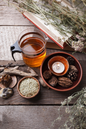 Healthy herbal tea preparation with glass asian teapot, candle. wooden and stone details and vintage rustic wooden background, monochrome, relax concept Stock Photo