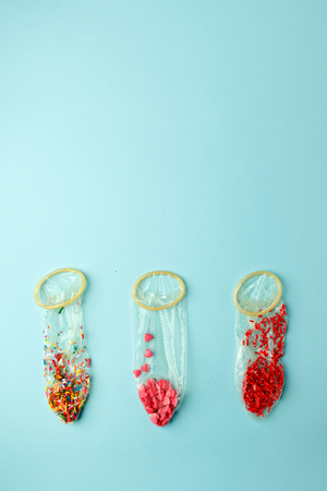Kondome gefüllt mit buntem Konfetti und Süßwarendressing
