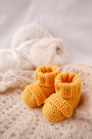 Children's yellow knitted booties on a light gentle background. The concept of expecting a child, motherhood, parenthood, the idea of a gift for a newborn