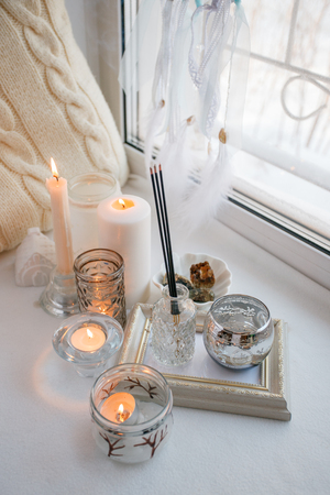 Shabby chic home design. Beautiful decoration table with a candles, dreamcacher, aroma stick on the windowsill, mindfullness relax concept Stock Photo