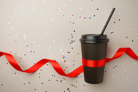Black paper cup of coffee to go and red silk ribbon on gray background with confetti, mock up, stylish festive concept, love coffe and valentine day creative idea Banque d'images