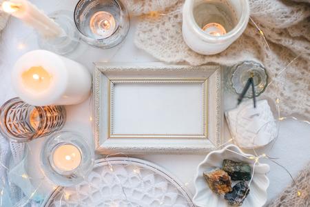 Fond monochrome blanc de printemps hiver confortable et doux, écharpe tricotée, capteur de rêves et bougies sur le rebord de la fenêtre. Vacances de Noël, chill, calme, relax à la maison Banque d'images