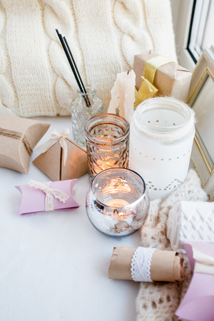 Cosy and soft winter spring white monochrome background, knitted pillow and candles on windowsill board. Christmas holidays, chill, calmness, relax at home Banco de Imagens