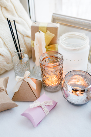 Beautiful gift box with bow and candles on white windosill background, Valentines Day and Mothers Day concept Stock Photo