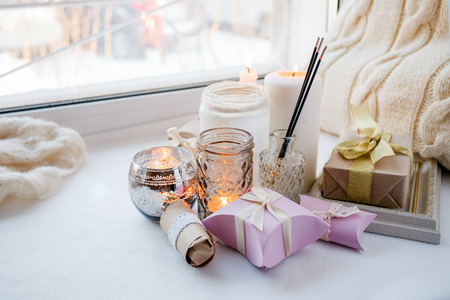 Home interior decor in brown colors: glass jar with aroma stick, candles and romance gift box on white windowsill. Living room decoration, cozy home, romantic relax background