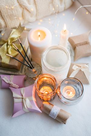 Stylish still life with gift boxes, candle sticks, burning candles, garland on light windowsill background, boho romance concept background and style