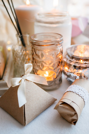 still life with interior details and burning candles in the living room, the concept of home comfort and interior, romantic gift boxes