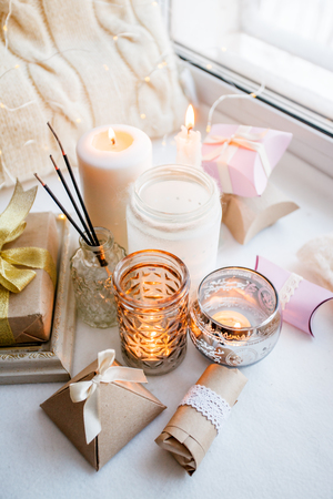 paraffin wax candles and one tealight in a glass candle holder and aroma stick, romantic gift boxes, standing on a windowsill early morning, concept of romance holiday, valentine day still life Stock Photo