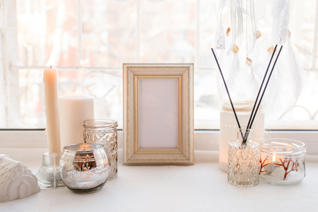 Details of still life in the home interior. Aroma stick, interior items, candles, frame for text, Moody. Cosy autumn winter light concept. Copy space, monochrome background